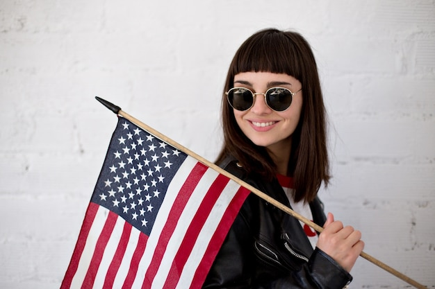Feminine beautiful woman or teenage girl wears new sunglasses eyewear in front of american flag, trendy and fashionable hipster, patriot of usa