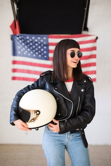 Bella donna femminile o ragazza adolescente indossa nuovi occhiali da sole davanti alla bandiera americana, hipster alla moda e alla moda, patriota degli stati uniti