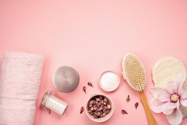 Feminine beauty and spa products, tools and cosmetics over the pink background