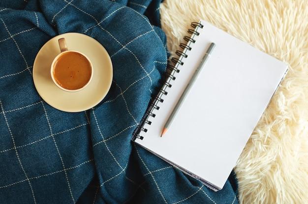 Женское рабочее место за столом блоггера со спиральной записной книжкой для планировщика дел и кофе на пушистой белой обложке и синем одеяле. мокап с копией пространства. вид сверху