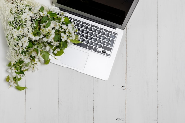 Feminine business concept with laptop, spring flowers bouquet and woman's hands holding cup of warm tea or coffee