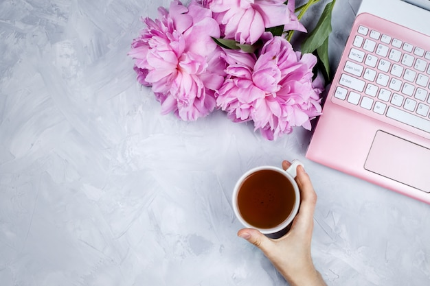 Feminine business mockup with pink laptop, peonies bouquet and woman's hand holding cup of warm tea