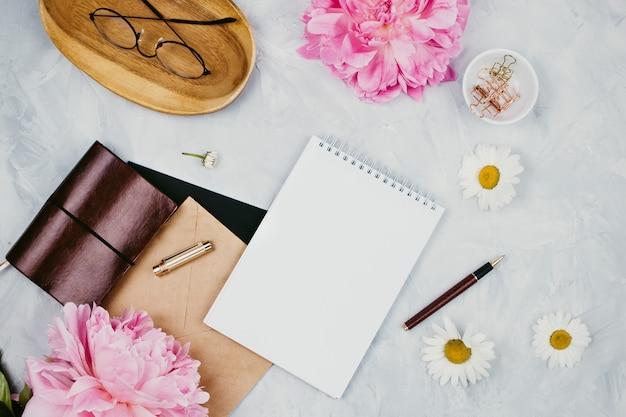 문구 용품, 데이지, 모란 꽃, 노트북 및 안경, 시멘트 배경에 flatlay가있는 여성 비즈니스 모형