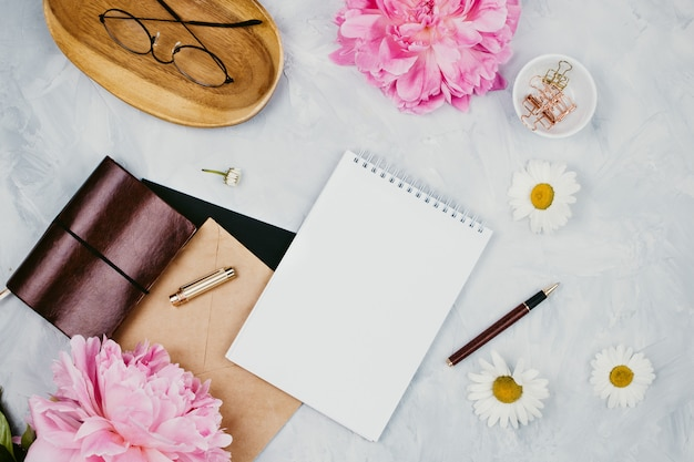 Feminine business mockup with stationery supplies, daisies, peony flowers, notebooks and glasses, flatlay on cement background