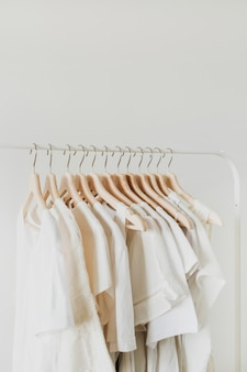 Feminine clothes on hanger. minimal fashion composition on white