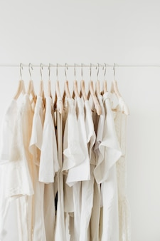 Feminine clothes on hanger. minimal fashion composition on white.
