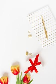 Женственная композиция женского рабочего пространства. подарок с красной лентой и букетом цветов тюльпанов, блокнотом и ручкой. плоская планировка и вид сверху