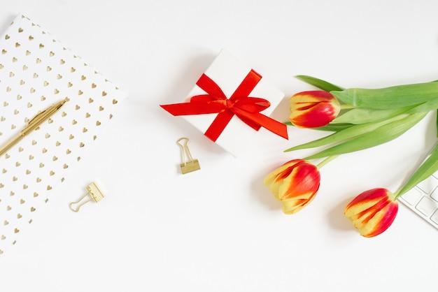 女性のワークスペースのフェミニンな構成。赤いリボンとチューリップの花の花束、ノートとペンが付いたギフト。フラットレイと上面図