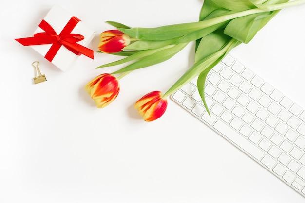 女性のワークスペースのフェミニンな構成。赤いリボンとチューリップの花の花束、キーボード付きのギフト。フラットレイと上面図