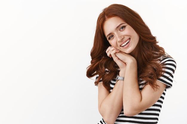 フェミニンなかわいい赤毛の女性は、素敵なロマンチックなシーンを考えて感動し、肩に頭を傾け、手のひらを一緒に押して喜んで面白がって、幸せそうに笑って、白い壁に立っています