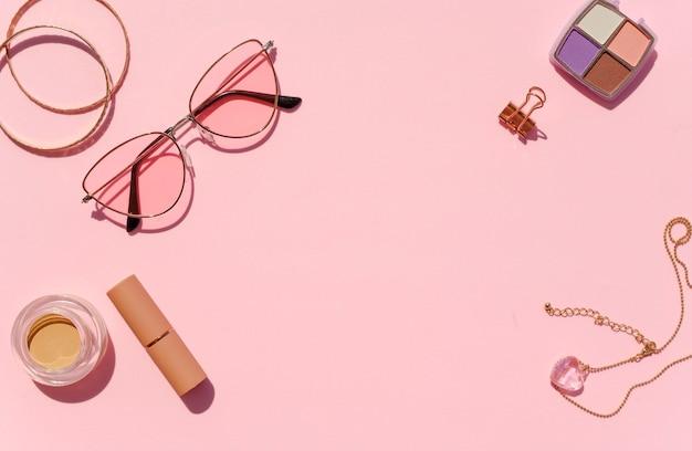 여성스러운 책상 프레임 모형. 분홍색 배경에 상위 뷰 화장품, 보석 및 선글라스. 프로모션을위한 공간