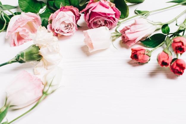 핑크 장미와 하얀 나무 배경에 꽃잎 여성 데스크 작업 영역 프레임. 평평한 누워, 평면도. 꽃 배경입니다. 여성의 날, 어머니의 날.