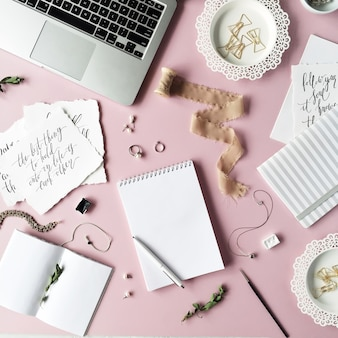 노트북, 일기, 리본이 달린 스풀, 서예 따옴표 및 분홍색의 황금색 클립이있는 여성스러운 책상 작업 공간.