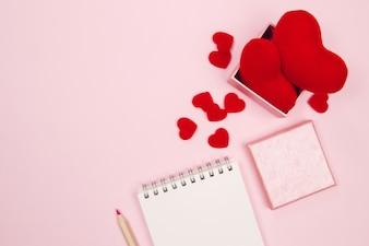 空のノートブック、ギフトボックス、赤い心臓をピンクのバックグラウンドでモチーフした女性用デスクワークスペース