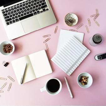 Женственное рабочее пространство стола с сочными, ноутбуком, очками, дневником и золотыми зажимами на розовом.