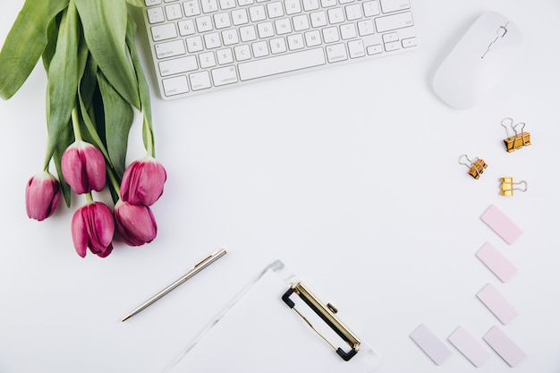 Feminine desk workspace with  tulips, computer keyboard, golden clips on white
