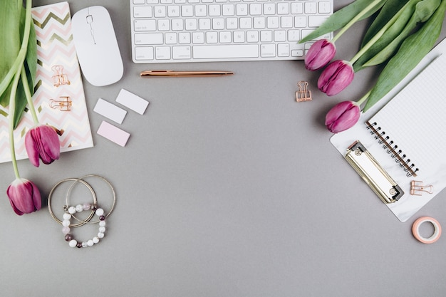 Feminine desk workspace with tulips, keyboard, diary and golden clips on grey