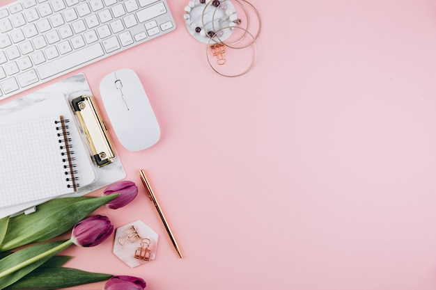 Feminine desk workspace with tulips, keyboard, golden clips on pink