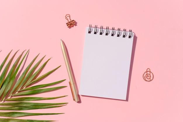 Макет женских дневниковых заметок. плоский лежал блокнот с ручкой и пальмовым листом на розовом фоне. копировать пространство