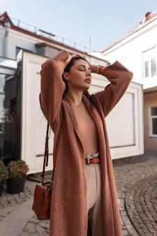 갈색 가죽 핸드백 유행 코트에서 여성 우아한 아름 다운 젊은 여자는 거리에 흰색 건물 근처 포즈. 섹시한 여자 패션 모델은 세련된 긴 머리를 곧게 만듭니다. 야외 뷰티 레이디.