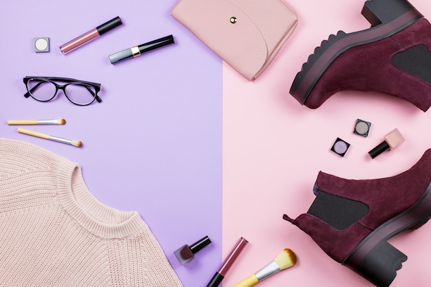 Feminine fashion autumn clothes, accessories and beauty products flat lay on a pastel background.