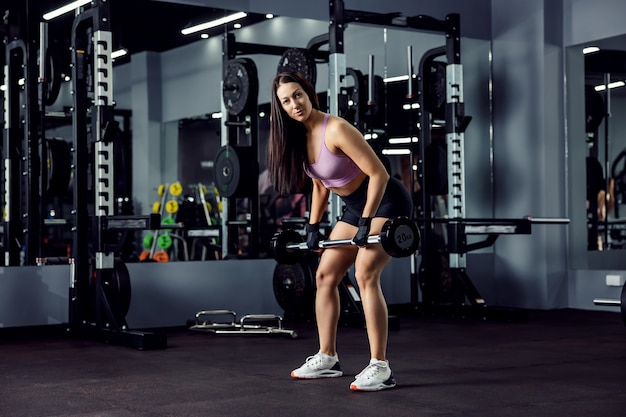 Feminine fitness brunette does arm and upper body exercises and uses a barbell with gloves