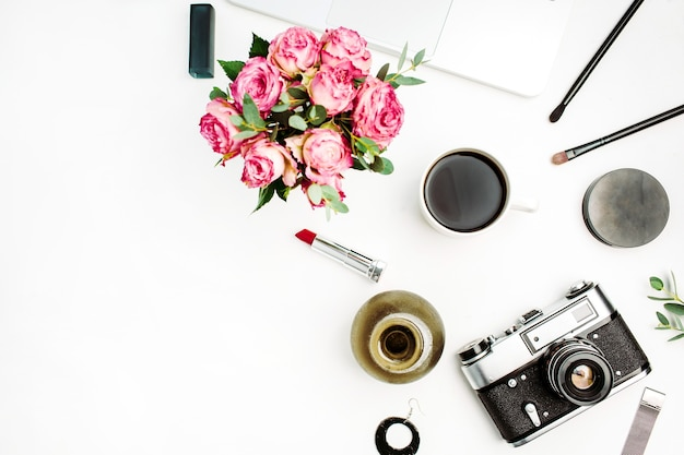 Feminine flat lay, top view workspace with rose flowers bouquet, vintage photo camera, coffee cup and accessories on white background