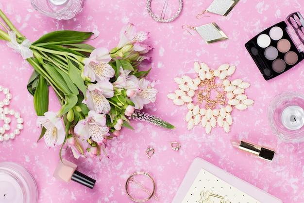 フェミニンなフラットレイアウトのファッションアクセサリーとピンクの花