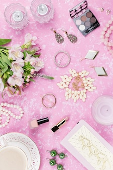 Feminine flat lay with woman fashion accessories, jewelry, cosmetics, coffee and flowers. top view
