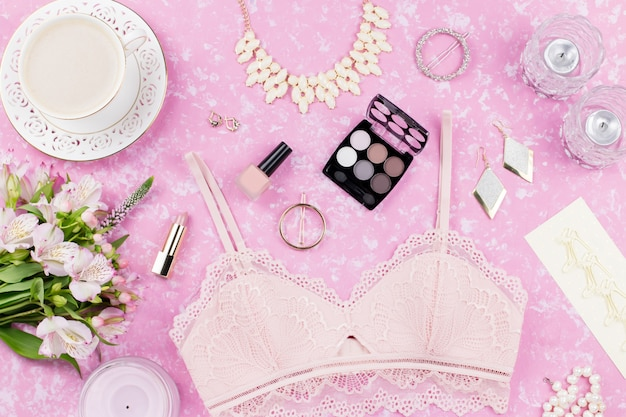 Feminine flat lay with woman fashion accessories, lingerie, jewelry, cosmetics, coffee and flowers. top view