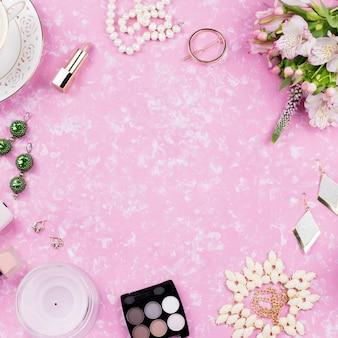 女性のファッションアクセサリー、ランジェリー、ジュエリー、化粧品、コーヒー、花が並ぶフェミニンなフラット。上面図
