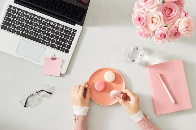 ノートパソコン、お茶、マカロン、写真カメラ、白い木製のテーブルの上に花とフェミニンなフラットレイワークスペース。上面図のモックアップ。