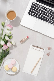 Feminine flat lay workspace with laptop, cup of tea, macarons, lipstick and flowers on white table