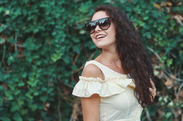 光沢のある白い笑顔の女性らしいフレッシュなサングラスモデル