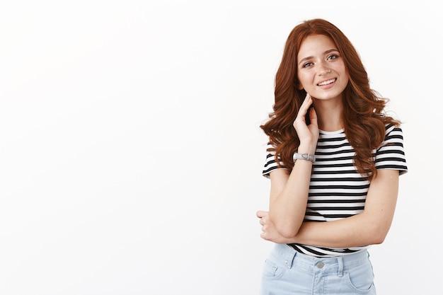 줄무늬 티셔츠에 주근깨가 있는 잘 생긴 빨간 머리 소녀, 머리를 기울이고, 한 팔을 교차하고 기뻐하며 웃고, 깨끗한 피부를 만지고, 여드름 흠집을 없애고, 흰 벽