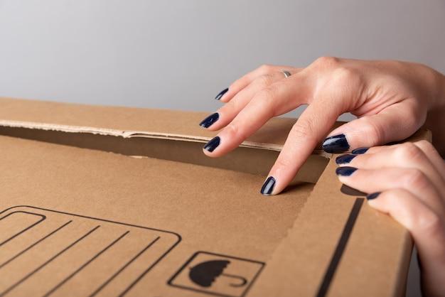 フェミニンな手がカートンボックスのカット部分を分割し、コピースペースのあるティッシュペーパーの窓から光線が入るようにします