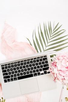 ノートパソコン、ピンクのアジサイの花の花束、パステルブランケット、モンスターの葉のプレートと白い表面のアクセサリーとフェミニンなホームオフィスデスク