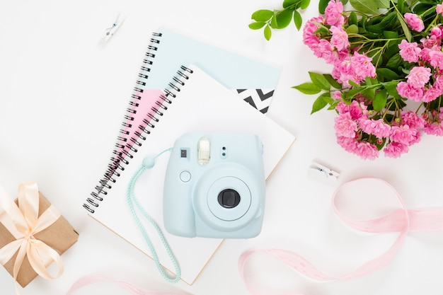 Feminine home office desk with modern instant film camera,paper notebook and notepad, bouquet of pik flowers, gift box, ribbon