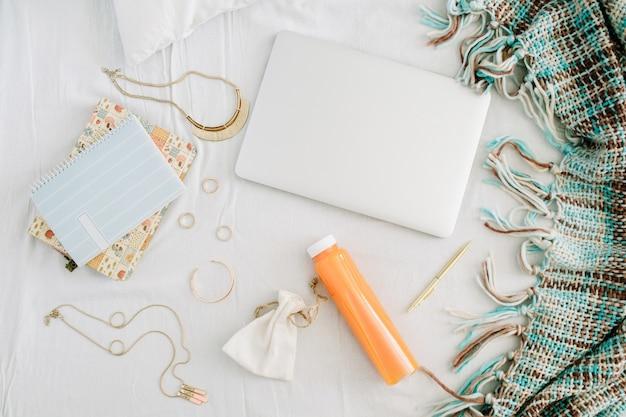 Женский домашний офис в постели с ноутбуком, дневником, бутылкой свежего сока, женскими аксессуарами на белом листе и пледе