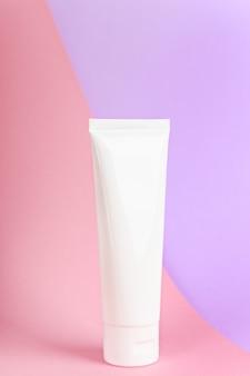 Женский гигиенический тубус на пастельно-розово-сиреневом фоне.