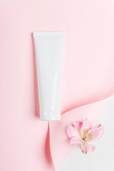 Женский гигиенический тюбик продукта на пастельно-розовом фоне.