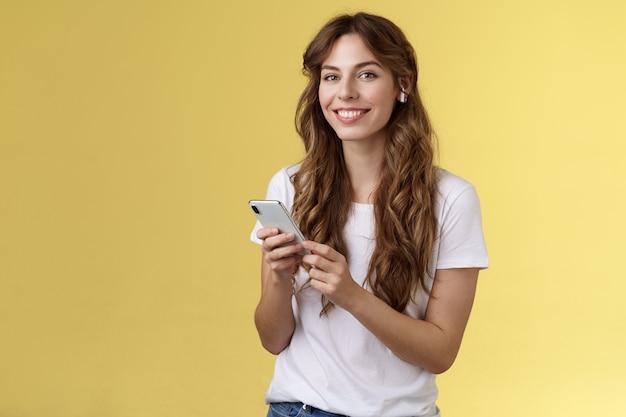 여성스러운 곱슬머리 여성 흰색 티셔츠를 들고 있는 스마트폰은 멋진 신곡을 들고 무선 이어폰을 끼고 음악을 듣고 기뻐하며 카메라는 노란색 배경을 즐긴다