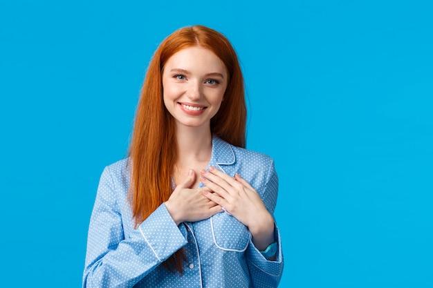 パジャマを着て、長い生姜髪のフェミニンな美しい赤毛の女性が心に手をつなぐ