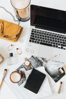 白い表面にラップトップ香水時計口紅ブラシアクセサリーを備えたフェミニンなモダンなホームオフィスデスクワークスペースフラットレイトップビューファッションブログソーシャルメディアウェブサイト最小限の構成
