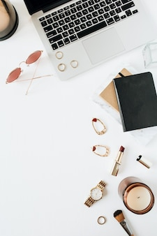 白い表面にラップトップウォッチの口紅サングラスアクセサリーを備えたフェミニンでモダンなホームオフィスデスクワークスペースフラットレイトップビューファッションブログソーシャルメディアウェブサイト最小限の構成
