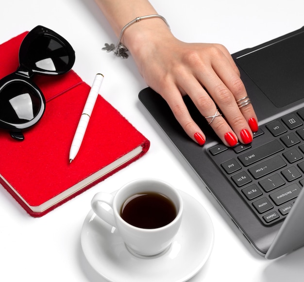 Feminine office table with laptop, notebook, pen, coffee and sunglasses.