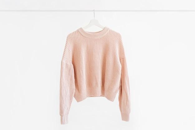 Feminine pale pink warm sweater on hanger on white background.