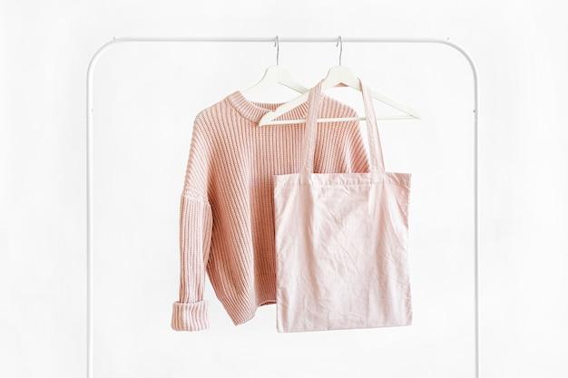 白い背景のハンガーにエコバッグとフェミニンな淡いピンクの暖かいセーター。エレガントなジャンパーファッションの衣装。春のワードローブ。最小限のコンセプト。