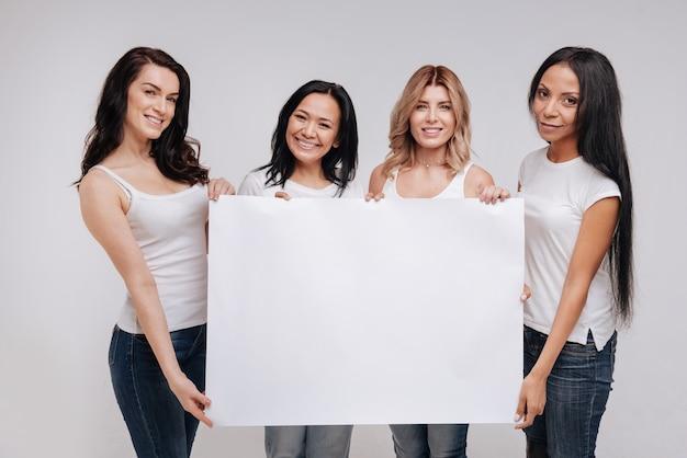 여성스러운 파워. 독립적이고 창의적인 매력적인 여성들이 함께 서있는 동안 관심을 끌고 있습니다.