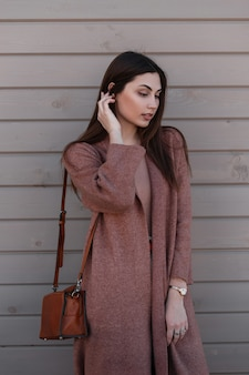 여성 예쁜 귀여운 젊은 여자가 머리카락을 곧게 펴고 아래로 보입니다. 세련 된 가죽 갈색 핸드백과 세련 된 긴 코트에서 아름 다운 여자는 거리에 빈티지 목조 건물 근처 포즈. 캐주얼 복장